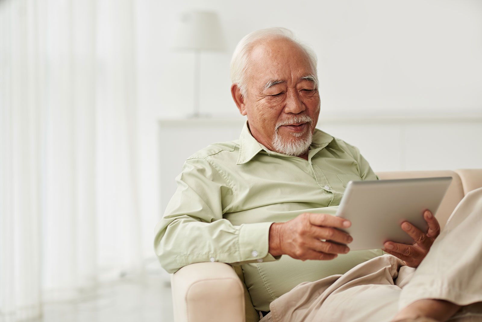 stock-photo-senior-vietnamese-man-sitting-on-sofa-and-reading-new-on-his-tablet-computer-401595523